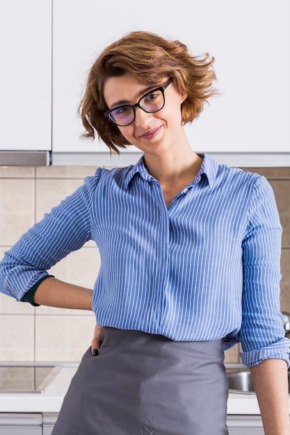 Portrait d'une jeune femme souriante avec sa main sur les hanches en regardant la caméra Photo gratuit