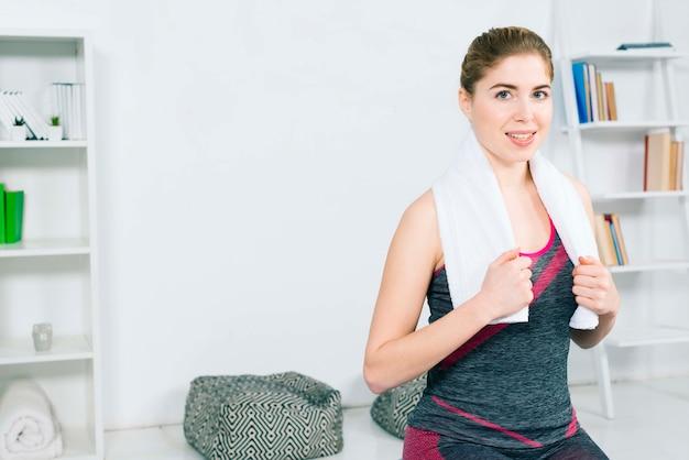 Portrait d'une jeune femme souriante avec une serviette blanche autour du cou en regardant la caméra Photo gratuit