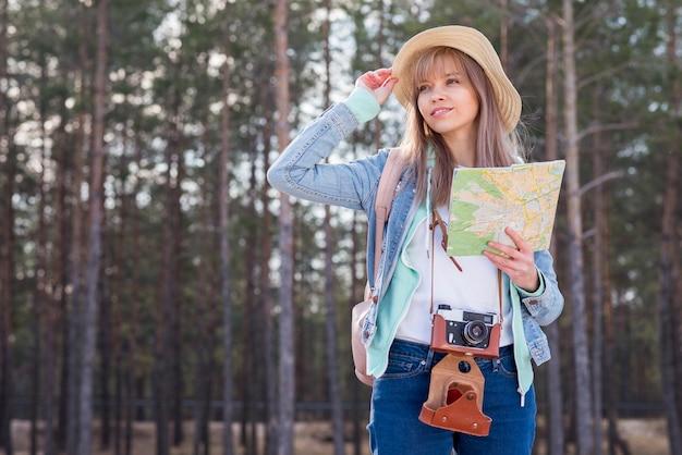 Portrait d'une jeune femme souriante tenant la carte en main Photo gratuit