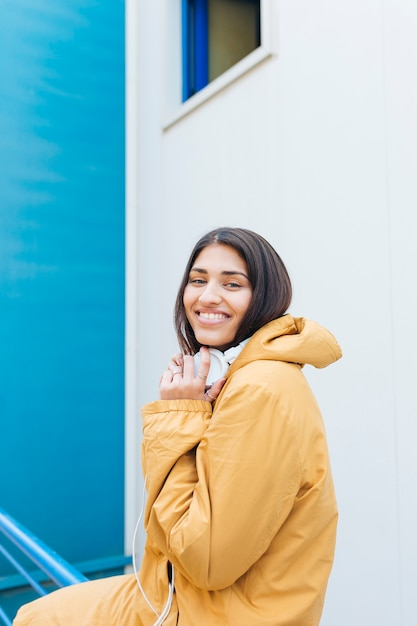 Portrait de jeune femme souriante tenant un casque sur son cou Photo gratuit