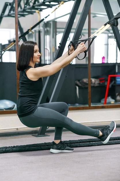 Portrait de jeune femme sportive, entraînement avec système de boucle de fitness Photo Premium