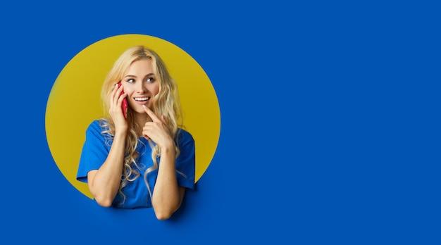 Portrait De Jeune Femme Surprise Debout Sur Un Mur Bleu. Femme Peep Hors D'un Trou Dans Le Mur. Espace Vide Pour Le Texte. Photo Premium