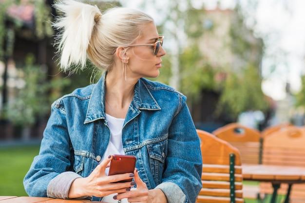 Portrait d'une jeune femme avec un téléphone portable à la recherche de suite Photo gratuit