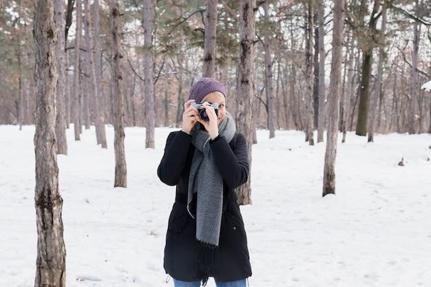 Portrait De Jeune Femme Tenant La Caméra Dans Le Paysage Enneigé Photo gratuit