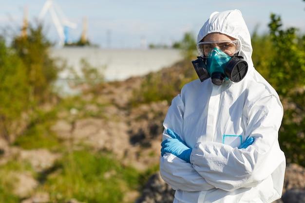 Portrait De Jeune Femme En Tenue De Travail Protectrice Et Masque Debout, Les Bras Croisés. Elle Travaille Dans Une Zone Dangereuse Photo Premium
