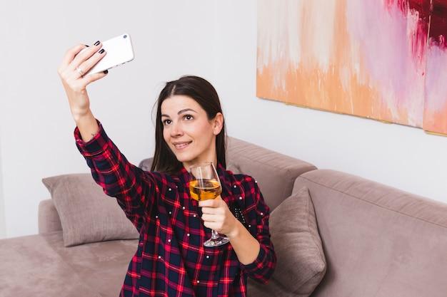 Portrait, Jeune, Femme, Tenue, Verre Vin, Prendre, Selfie, Sur, Téléphone Portable, Chez Soi Photo gratuit