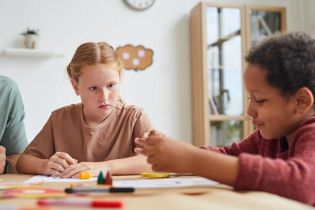 Portrait De Jeune Fille Aux Cheveux Rouges Taches De Rousseur Regardant Un Ami Tout En Dessinant Des Images Ensemble Pendant Les Cours D'art à L'école Photo Premium