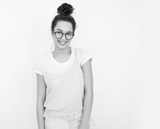 Portrait De Jeune Fille Brune Belle Modèle De Fille Avec Du Maquillage Nude Dans Des Vêtements De Hipster Rose D'été Coloré Posant Près Du Mur. Regardant Joyeusement Photo gratuit