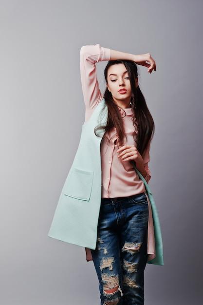 Portrait, de, jeune fille brune, porter, dans, chemisier rose, veste turquoise, déchiré, jean Photo Premium