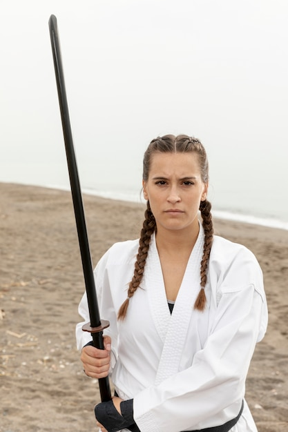 Portrait de jeune fille en costume de karaté avec épée Photo gratuit