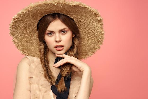 Portrait D'une Jeune Fille Dans Un Chapeau De Paille Sur Un Gros Plan D'émotions Rose Tresses De Modèle Beau Visage. Photo Premium