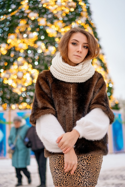 Portrait d'une jeune fille dans un manteau de fourrure sur le fond d'un sapin de noël. Photo Premium