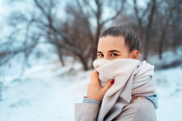 Portrait De Jeune Fille Dans Le Parc En Journée D'hiver, Portant Un Foulard, Sur Fond D'arbres Flous. Photo Premium