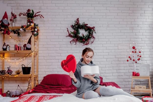 Portrait D'une Jeune Fille Dans Un Pull Gris Avec Un Coffret Rouge En Forme De Coeur Assis Dans L'appartement, Le Concept De La Saint-valentin, Copy Space Photo Premium