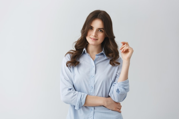 Portrait De Jeune Fille étudiante Aux Cheveux Noirs Ondulés En Chemise Bleue Avec Un Regard Confiant Et Un Sourire Doux. Photo gratuit
