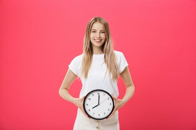 Portrait d'une jeune fille excitée vêtue d'un t-shirt blanc pointant au réveil Photo Premium