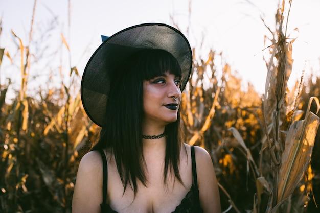 Portrait de jeune fille halloween costume sorcière dans un champ de maïs au coucher du soleil. belle jeune femme sérieuse au chapeau de sorcière aux longs cheveux noirs et aux lèvres noires Photo Premium