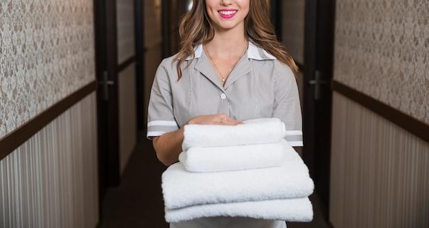 Portrait de jeune fille heureuse, debout dans le couloir, tenant des serviettes douces pliées Photo gratuit
