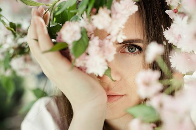 Portrait de jeune fille parmi les fleurs de sakura se bouchent Photo gratuit