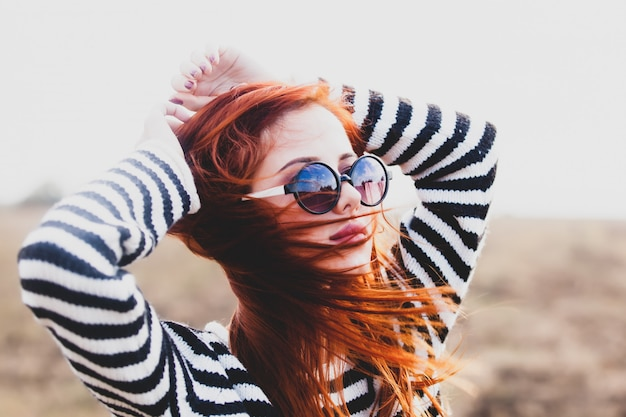 Portrait d'une jeune fille rousse à lunettes de soleil Photo Premium