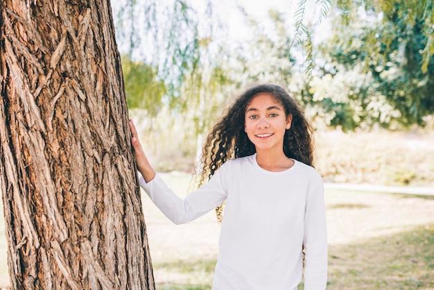 Portrait de jeune fille souriante, debout près de l'arbre, regardant la caméra Photo gratuit