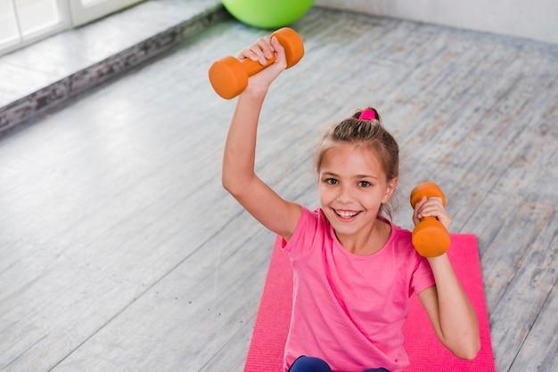 Portrait d'une jeune fille souriante exerçant avec un haltère orange Photo gratuit