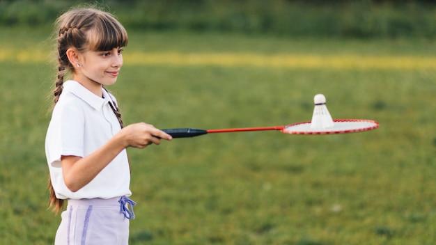 Portrait d'une jeune fille souriante jouant au badminton Photo gratuit
