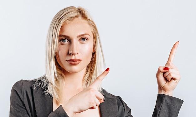 Portrait D'une Jeune Fille Souriante Pointant Le Doigt Vers Le Haut à Copyspace Isolé Sur Fond Blanc. Une Femme Montre Une Idée, Un Lieu De Publicité. Blonde Positive. Photo Premium