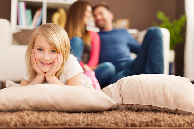 Portrait De Jeune Fille Souriante Se Détendre Sur Un Tapis Dans Le Salon Photo gratuit