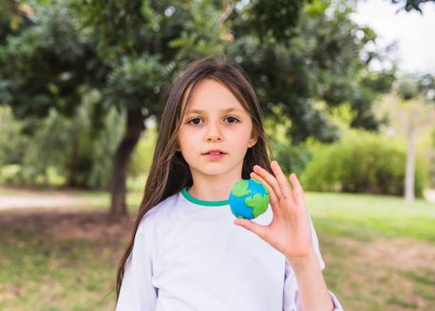 Portrait d'une jeune fille tenant un globe terrestre en argile à la main Photo gratuit