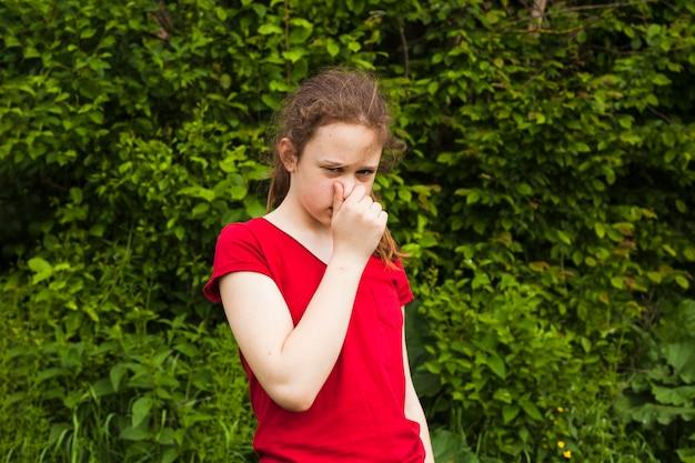 Portrait De Jeune Fille Tenant Le Nez Dans La Nature Verdoyante, Regardant La Caméra Photo gratuit