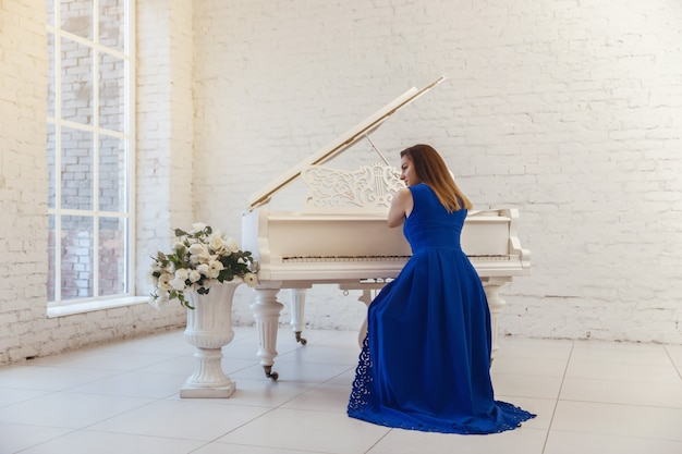 Portrait d'une jeune fille vêtue d'une robe bleue, assise au piano au centre de la pièce. vue arrière Photo Premium
