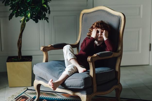Portrait d'un jeune garçon assis dans le fauteuil et s'appuyant sur sa main Photo Premium