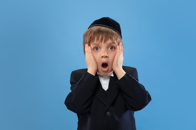 Portrait D'un Jeune Garçon Juif Orthodoxe Isolé Sur Studio Bleu Photo gratuit