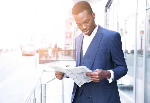 Portrait d'un jeune homme d'affaires africain debout en plein air au bureau, lisant le journal Photo gratuit