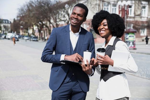 Portrait d'un jeune homme d'affaires africain et femme d'affaires détenant une tasse de café jetable dans la ville Photo gratuit