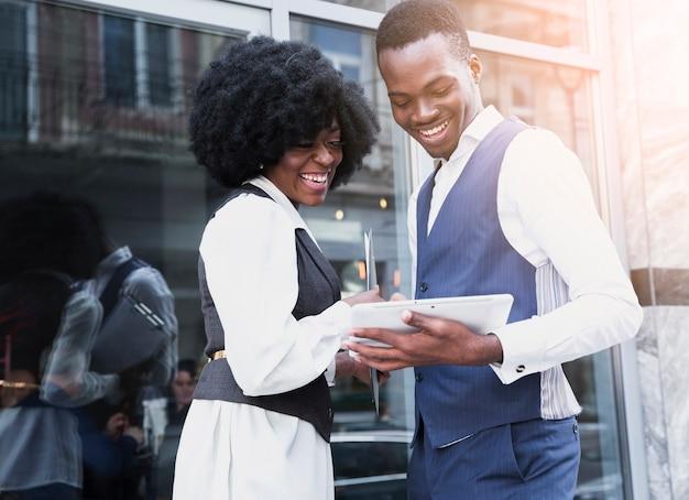 Portrait d'un jeune homme d'affaires africain souriant et femme d'affaires en regardant tablette numérique Photo gratuit