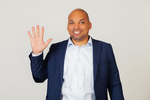 Portrait De Jeune Homme D'affaires Afro-américain Prospère, Montrant Avec Les Doigts Numéro Cinq, Souriant, Confiant Et Heureux. L'homme Montre Cinq Doigts. Numéro 5. Photo Premium