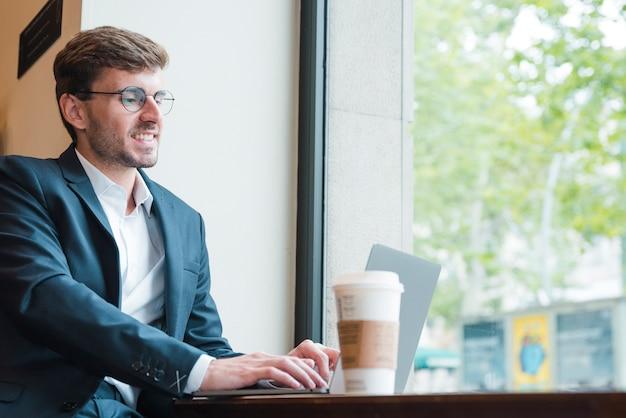 Portrait d'un jeune homme d'affaires à l'aide d'un ordinateur portable avec une tasse de café sur la table à café Photo gratuit