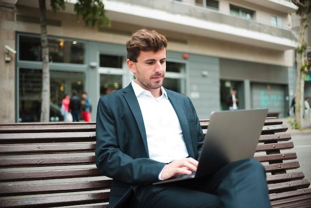 Portrait D'un Jeune Homme D'affaires Assis Sur Un Banc à L'aide D'un Ordinateur Portable Photo gratuit