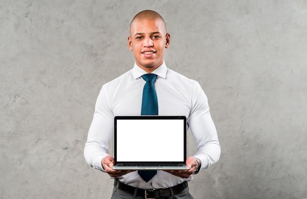 Portrait d'un jeune homme d'affaires confiant debout contre un mur gris montrant un ordinateur portable avec écran blanc Photo gratuit