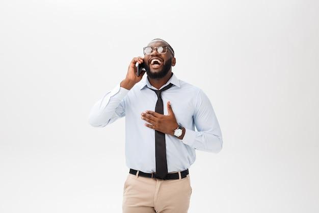 Portrait d'un jeune homme d'affaires confiant, parlant au téléphone cellulaire Photo Premium