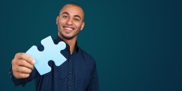 Portrait D'un Jeune Homme D'affaires Heureux Tenant Un Puzzle Photo Premium