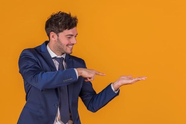 Portrait, jeune, homme affaires, pointage, doigt, quelque chose, contre, a, orange, fond Photo gratuit
