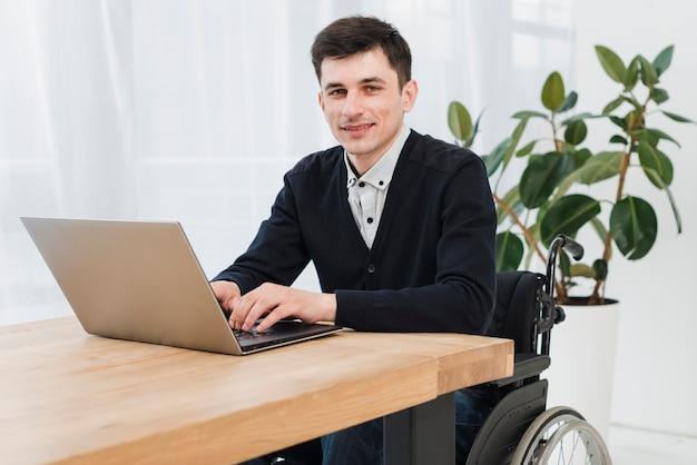 Portrait D'un Jeune Homme D'affaires Souriant Assis Sur Un Fauteuil Roulant à L'aide D'un Ordinateur Portable Photo gratuit