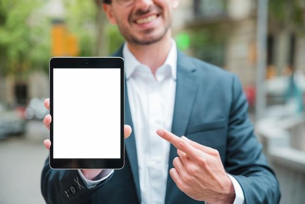 Portrait d'un jeune homme d'affaires souriant, pointant son doigt vers la tablette numérique Photo gratuit