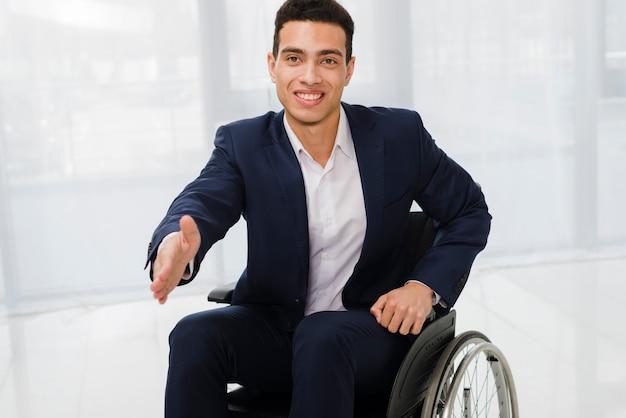 Portrait d'un jeune homme d'affaires souriant tend la main vers la caméra Photo gratuit