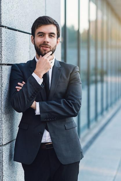 Portrait de jeune homme d'affaires tenant une barbe en costume posant sur le fond de l'immeuble de bureaux Photo Premium