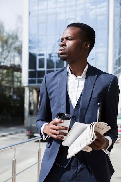 Portrait d'un jeune homme d'affaires tenant une tablette numérique; journal et tasse à café jetable Photo gratuit