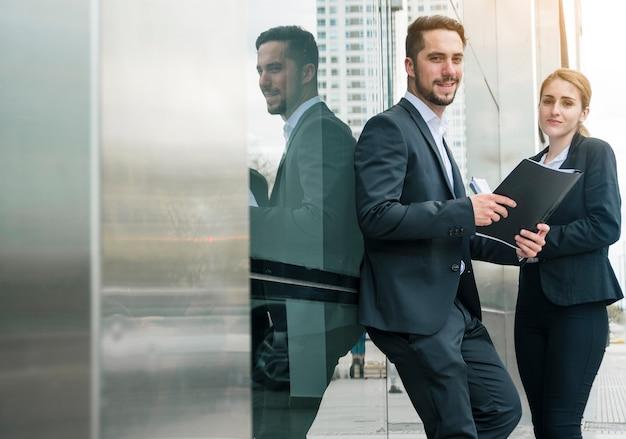 Portrait, jeune, homme affaires, tenue, dossier, main, debout, à, collègue, femme, dehors Photo gratuit